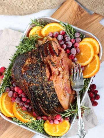 spiral cut ham in metal baking pan, orange slices, cranberries, fresh herbs, on cutting board.