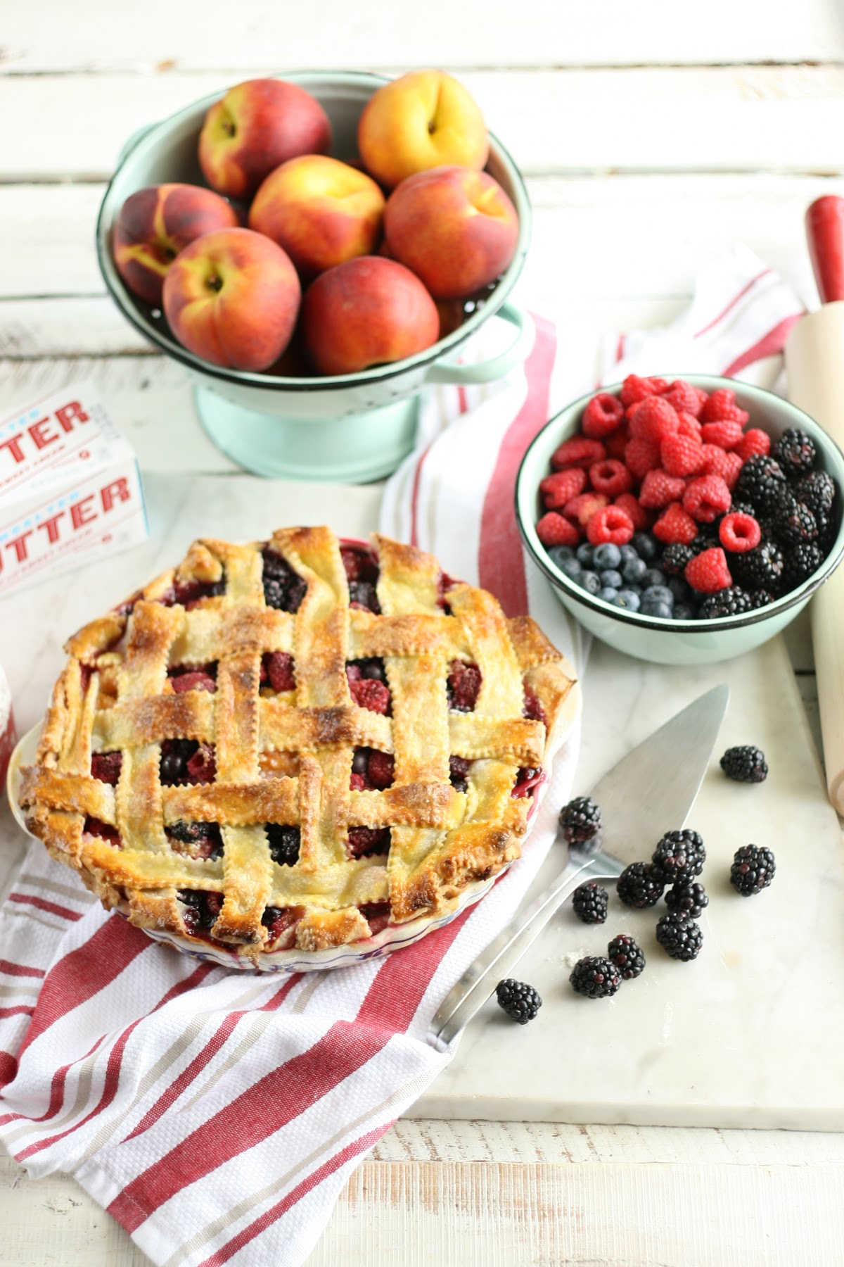 berry pie with lattice crust in blue floral pie dish, fruit in mint green enamelware strainer.