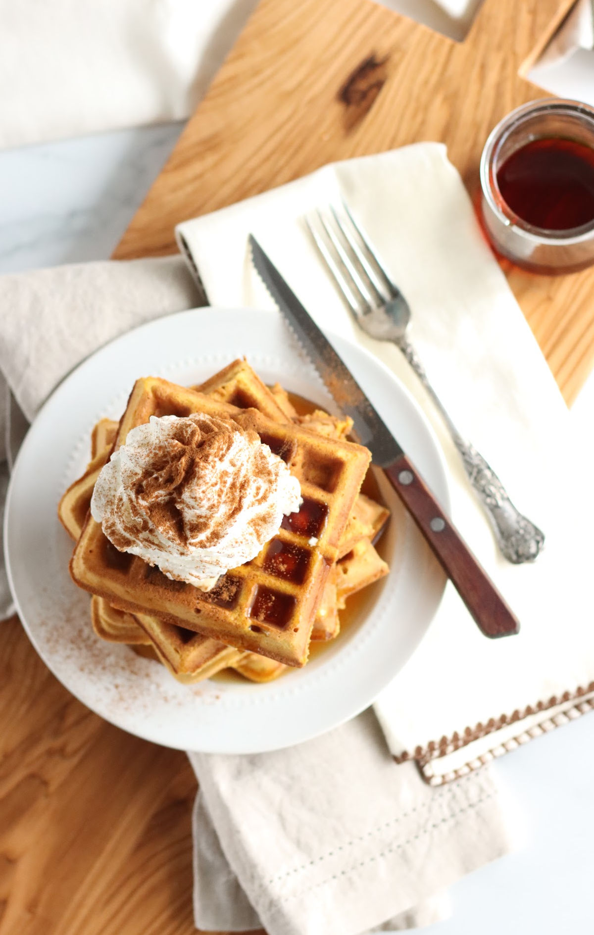 Square pumpkin waffles stacked on each other, whipped cream, maple syrup, and sprinkled with cinnamon.