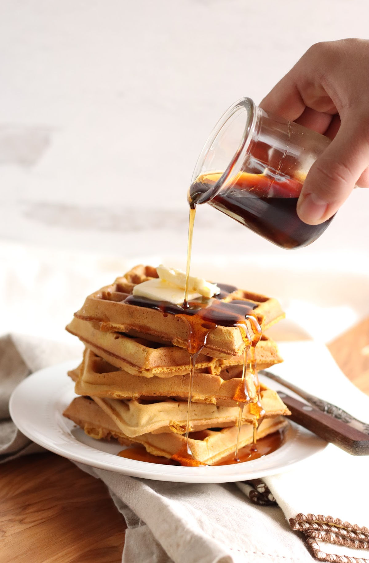 Square pumpkin waffles stacked on each other, topped with whipped cream, maple syrup, and ground cinnamon.