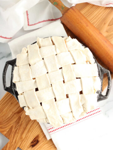 unbaked pie with lattice crust on wooden cutting board, wooden rolling pin to side.