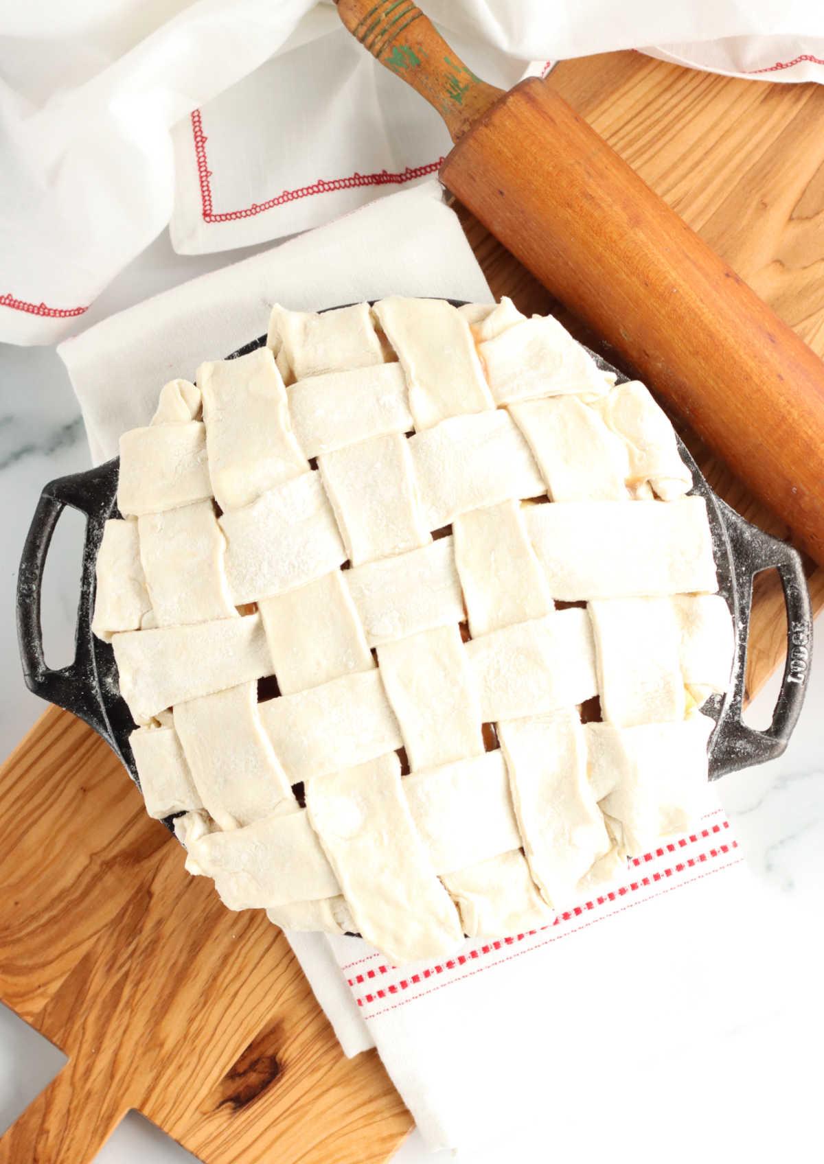 unbaked pie in cast iron pie plate with lattice crust.