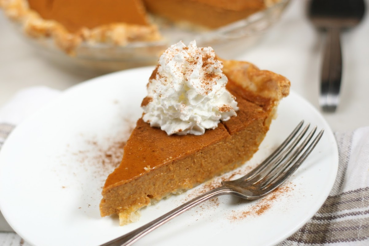 slice of pumpkin pie topped with whipped cream and cinnamon on white plate.