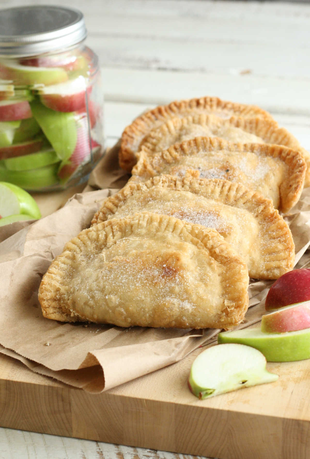 Four apple hand pies on wooden cutting board, slices of apples around them.