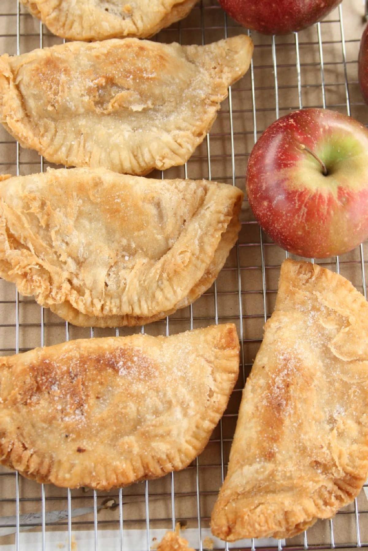 Apple hand pies cooling on metal baking rack. McIntosh apples on rack.