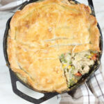 chicken pot pie with slice missing in dual handle cast iron skillet on taupe kitchen towel.