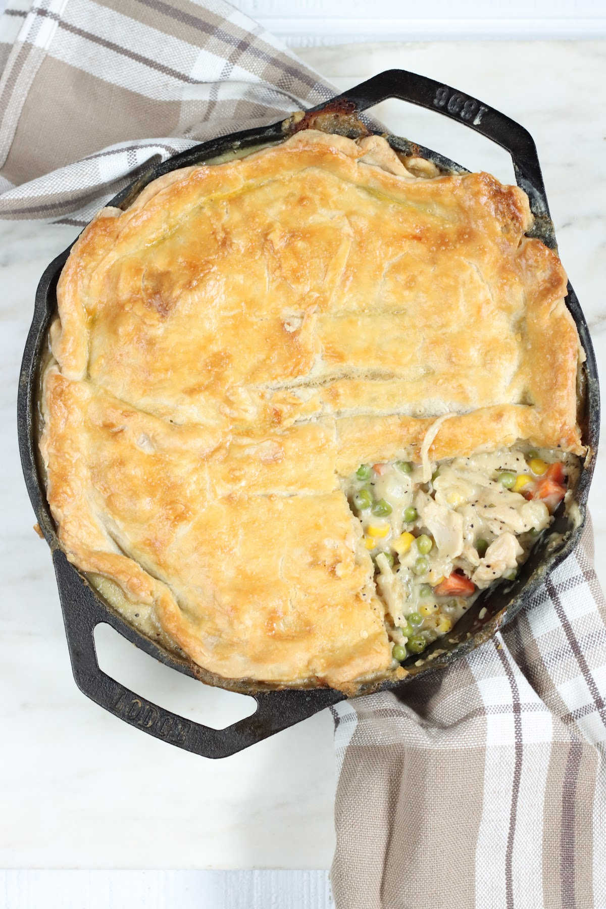 Chicken pot pie with one slice out in dual-handle cast iron pan on white marble.