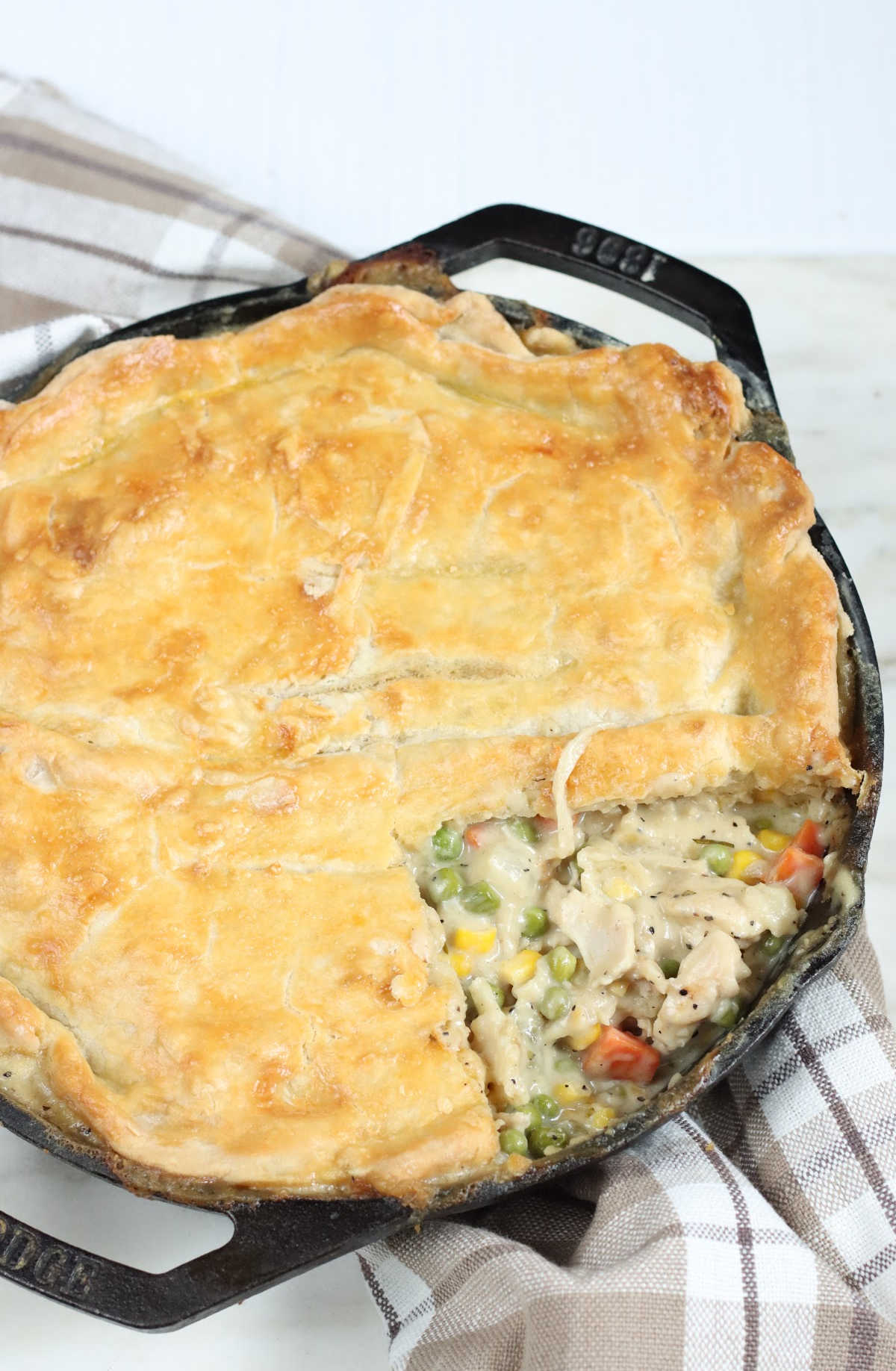 Close up of chicken pot pie with slice missing in dual handle cast iron skillet.