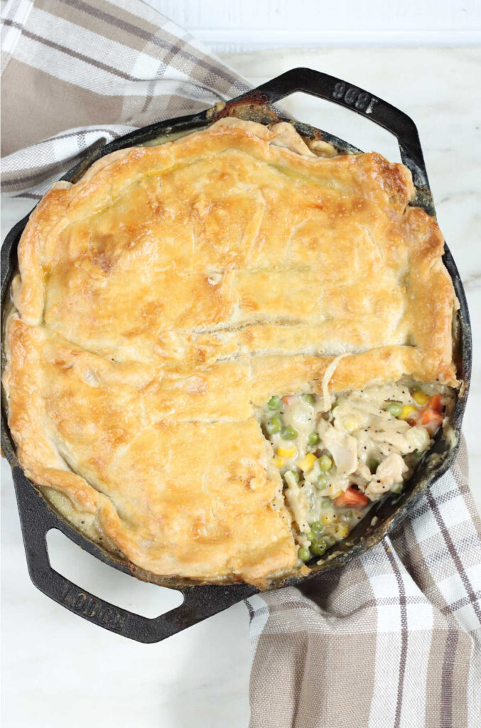 Chicken pot pie in dual handle cast iron pan with slice missing.