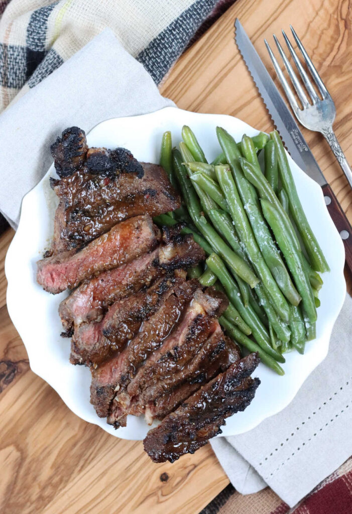 Ribeye steak sliced on small white plate along side fresh green beans sprinkled with salt.