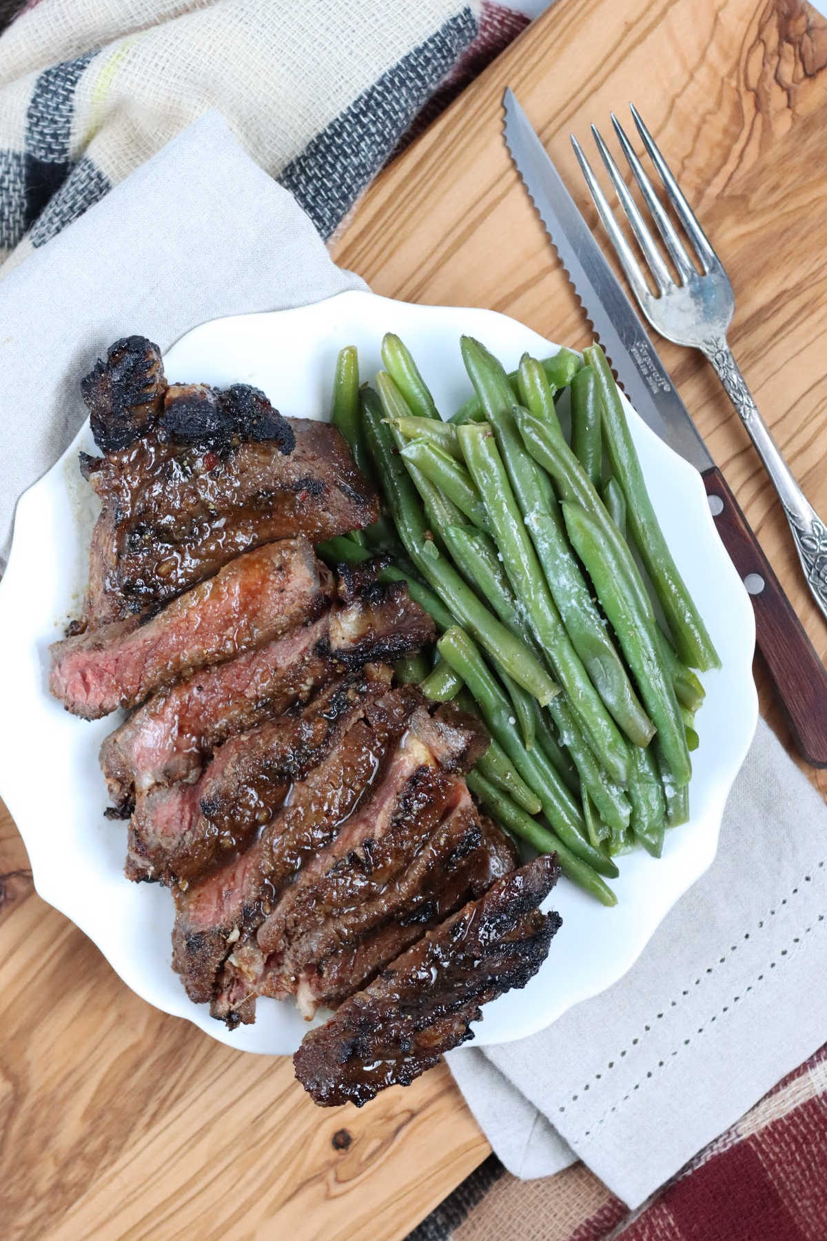 Sliced grilled steak on small white plate with side of fresh green beans.