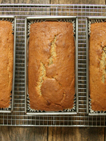 Three loaves of banana bread in metal loaf pans cooling on metal baking rack on reclaimed boards.