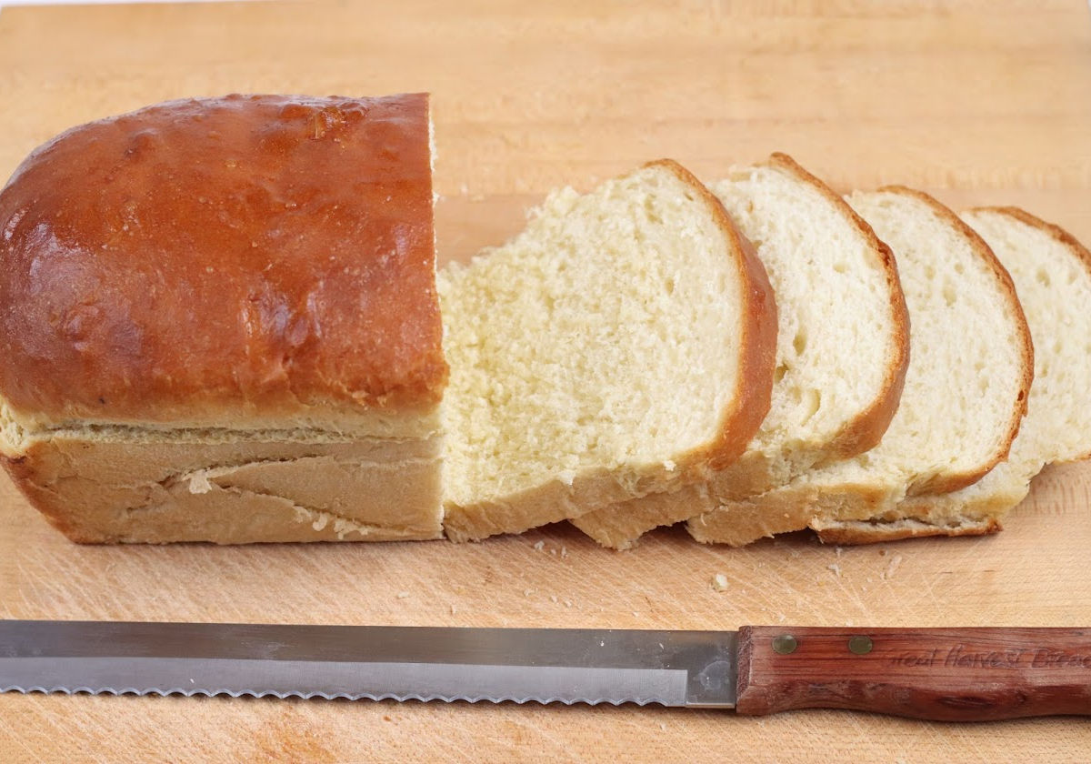 Loaf of bread partially sliced on wooden cutting board, wooden handle bread knife in front.