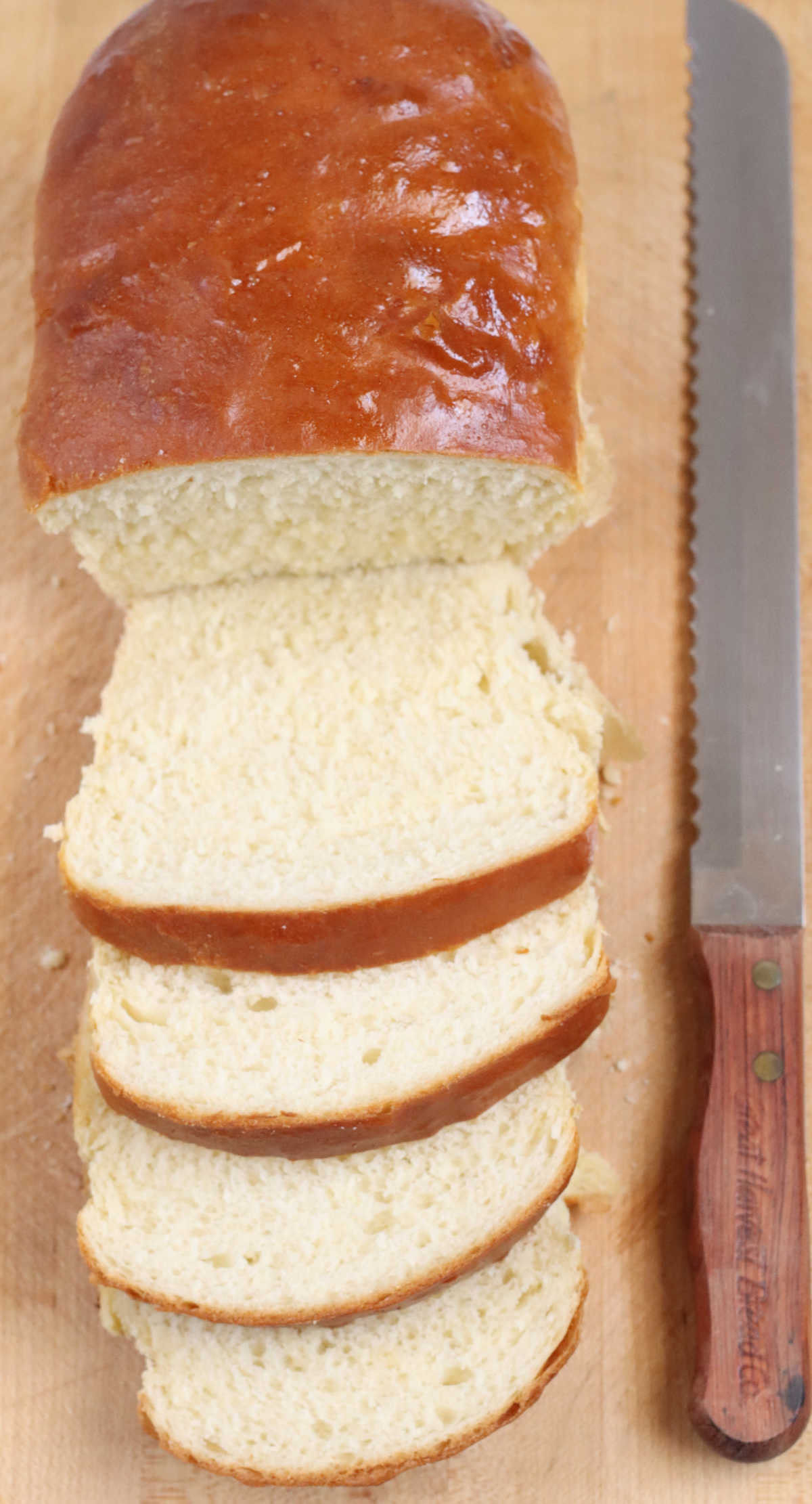 Loaf of white bread sliced partially on wooden cutting board with bread knife to right.