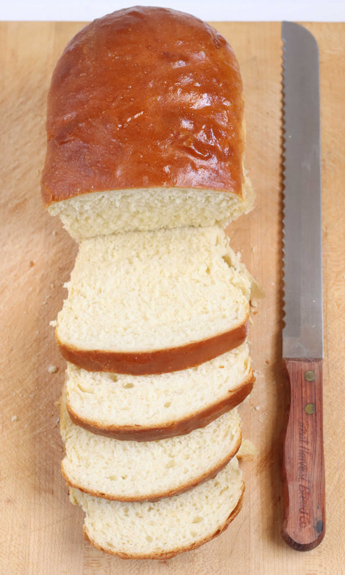 Loaf of white bread on wooden cutting board partially sliced, bread knife to right.