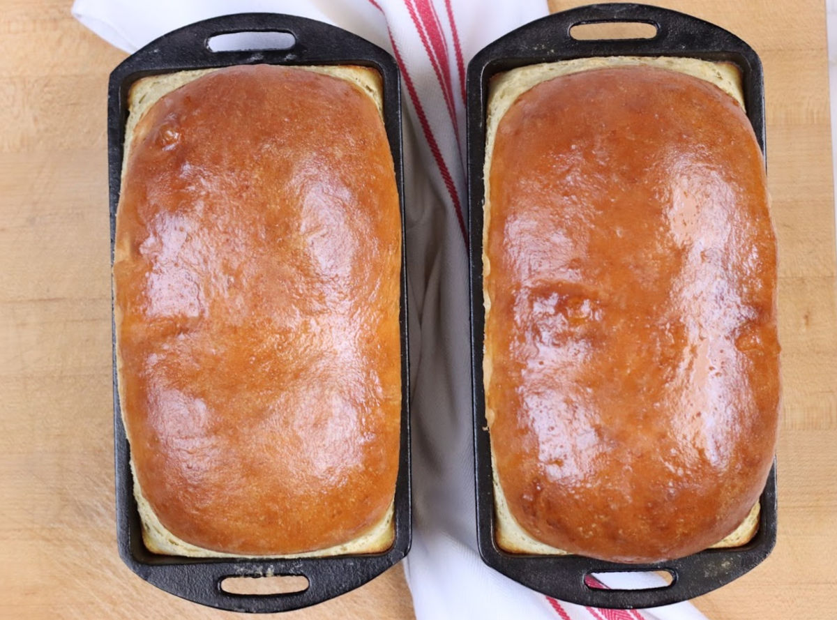 Two loaves of baked bread in cast iron loaf pans on wooden cutting board, overhead shot.