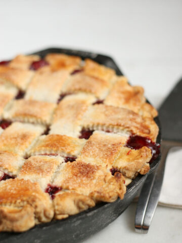 Cherry pie in dual handle cast iron pan with lattice crust, juices dripping out of pie.