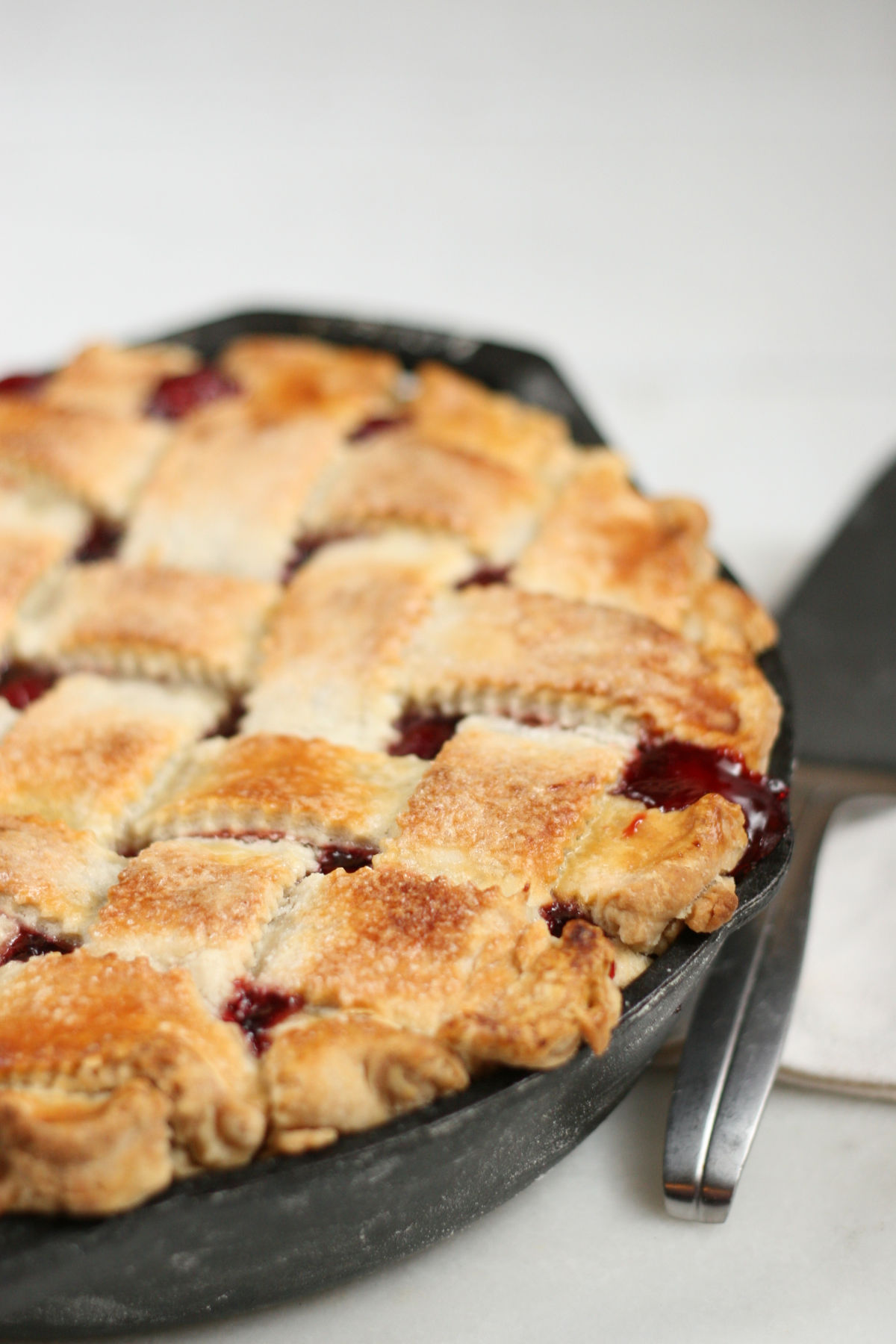 Cherry pie with weaved crust in cast iron skillet, cherry juices dripping out edge of pan.