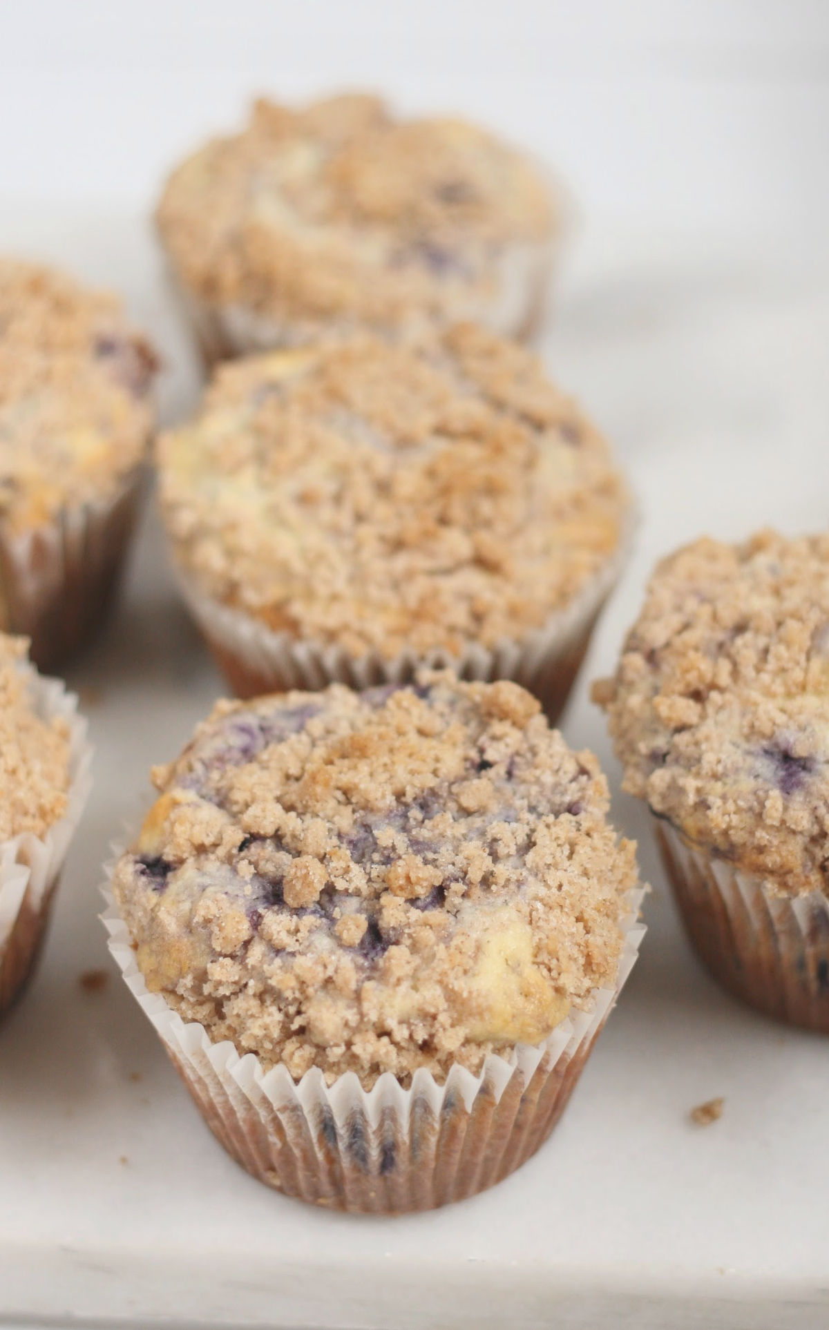 Blueberry muffins with crumb topping in paper liners on white marble,