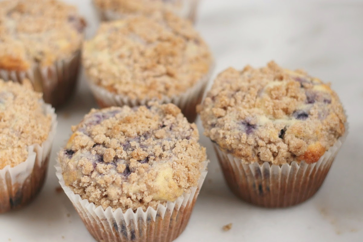 Blueberry muffins with crumb topping on white marble.