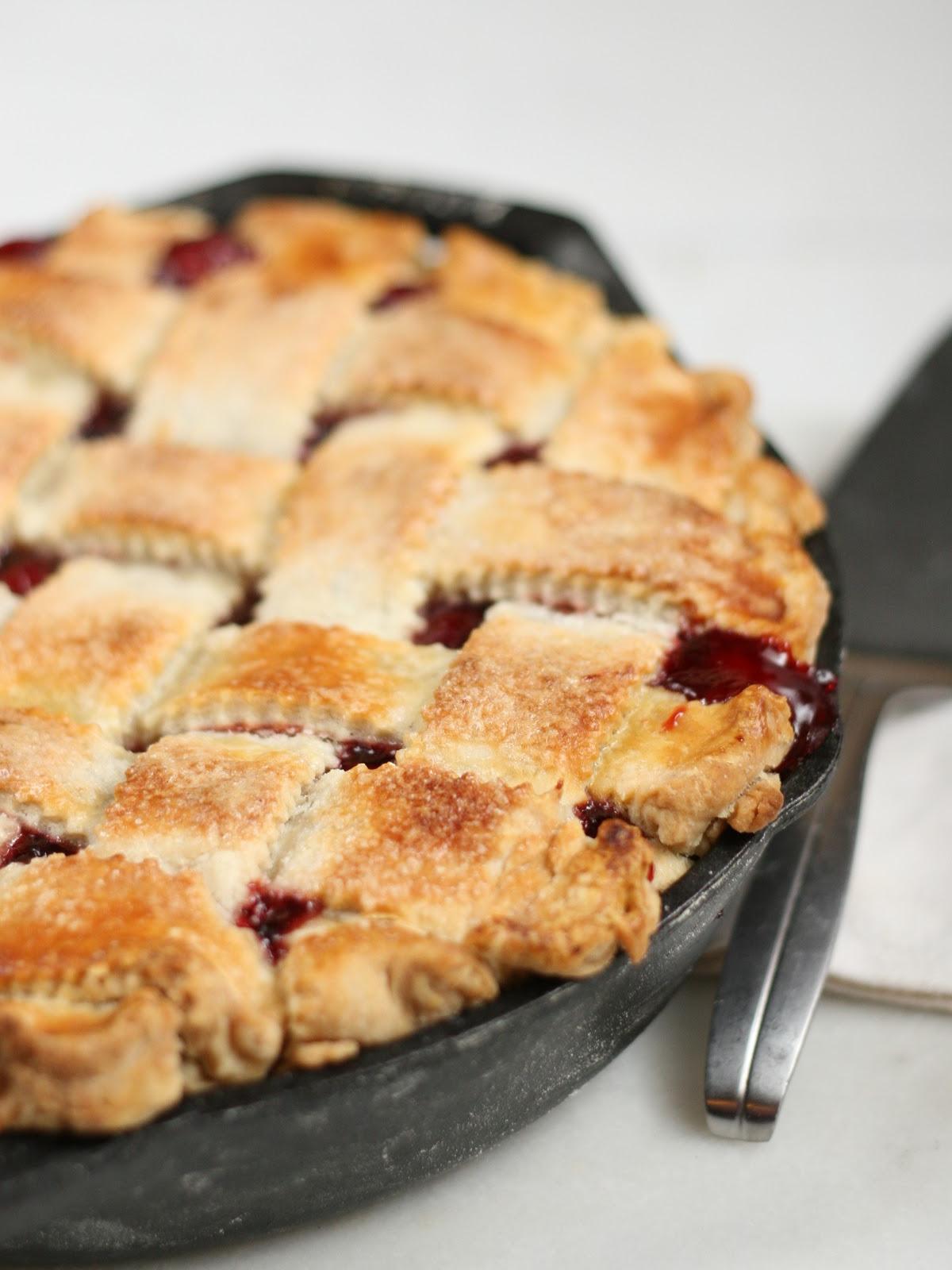 Cherry pie with lattice crust in dual handle cast iron skillet.