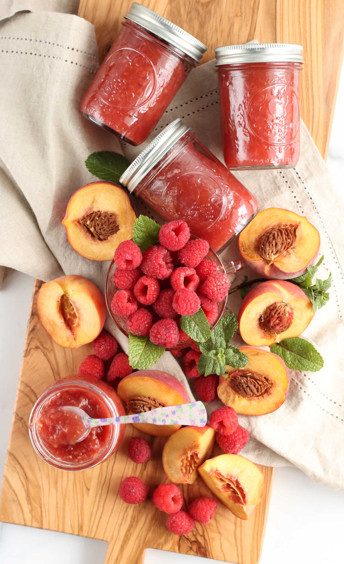 Three Mason jars with raspberry peach jam, fresh raspberries, peaches cut in half, fresh mint on wooden cutting board.