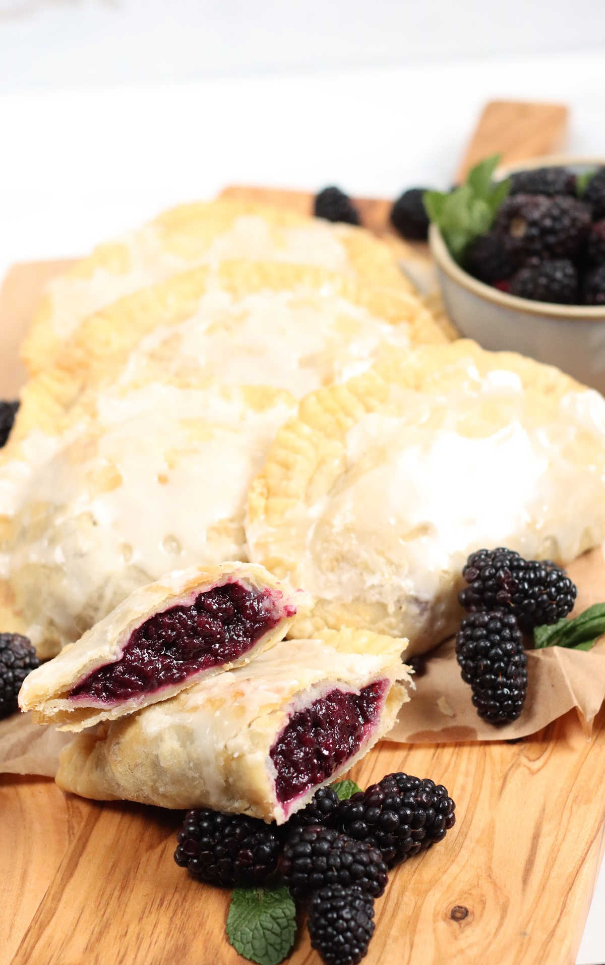 Close up of blackberry hand pie cut in half, other pies in background, loose blackberries.