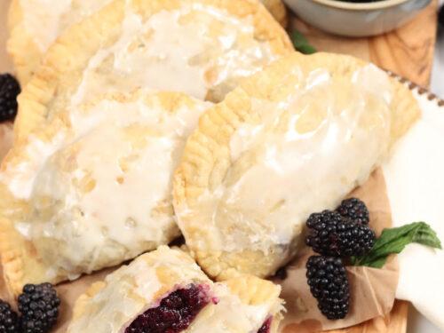 Blackberry hand pies on wooden cutting board, loose blackberries around.