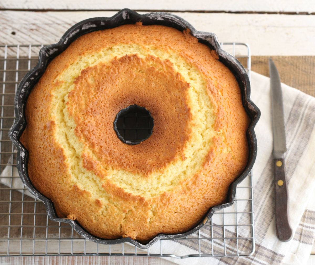 lemon cake in Bundt pan, cooling on baking rack.