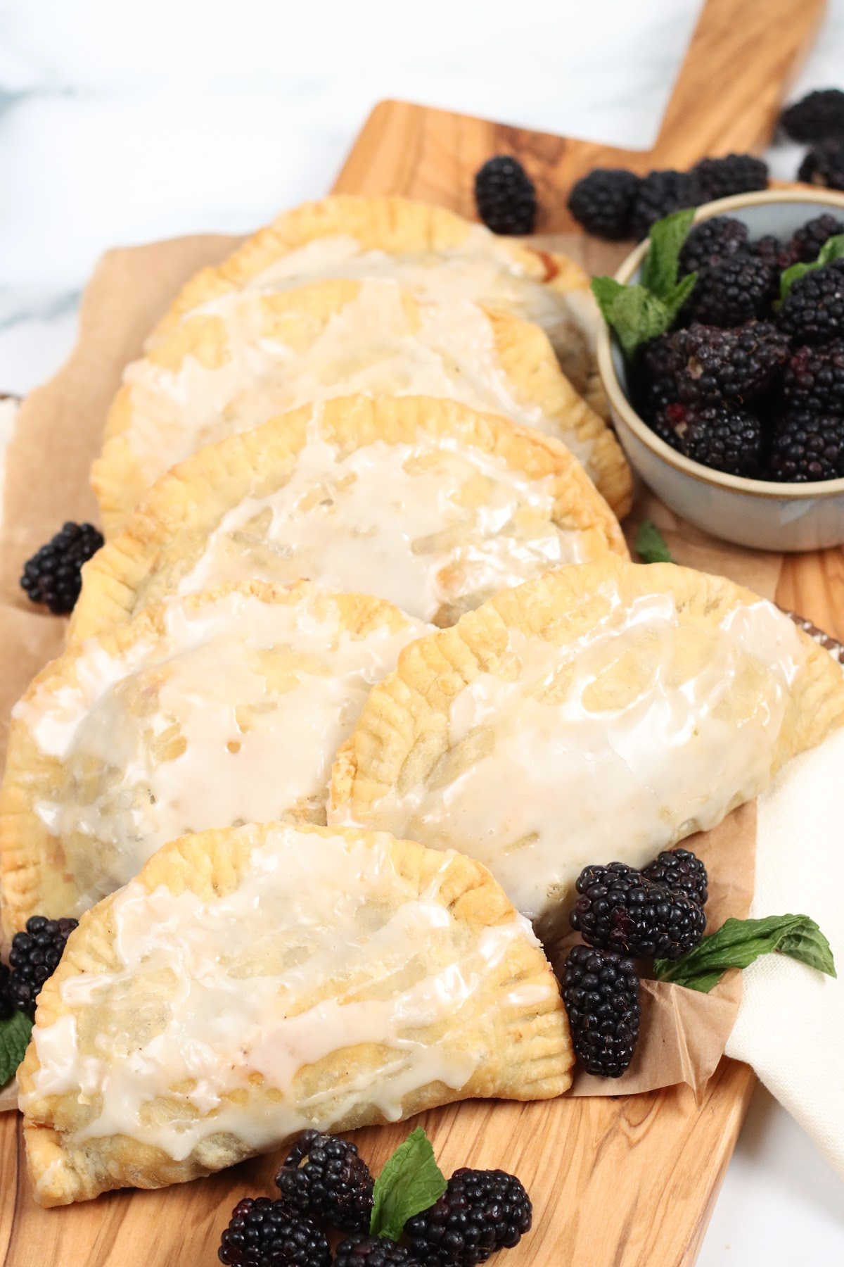 Blackberry hand pies and loose fresh blackberries on wooden cutting board.