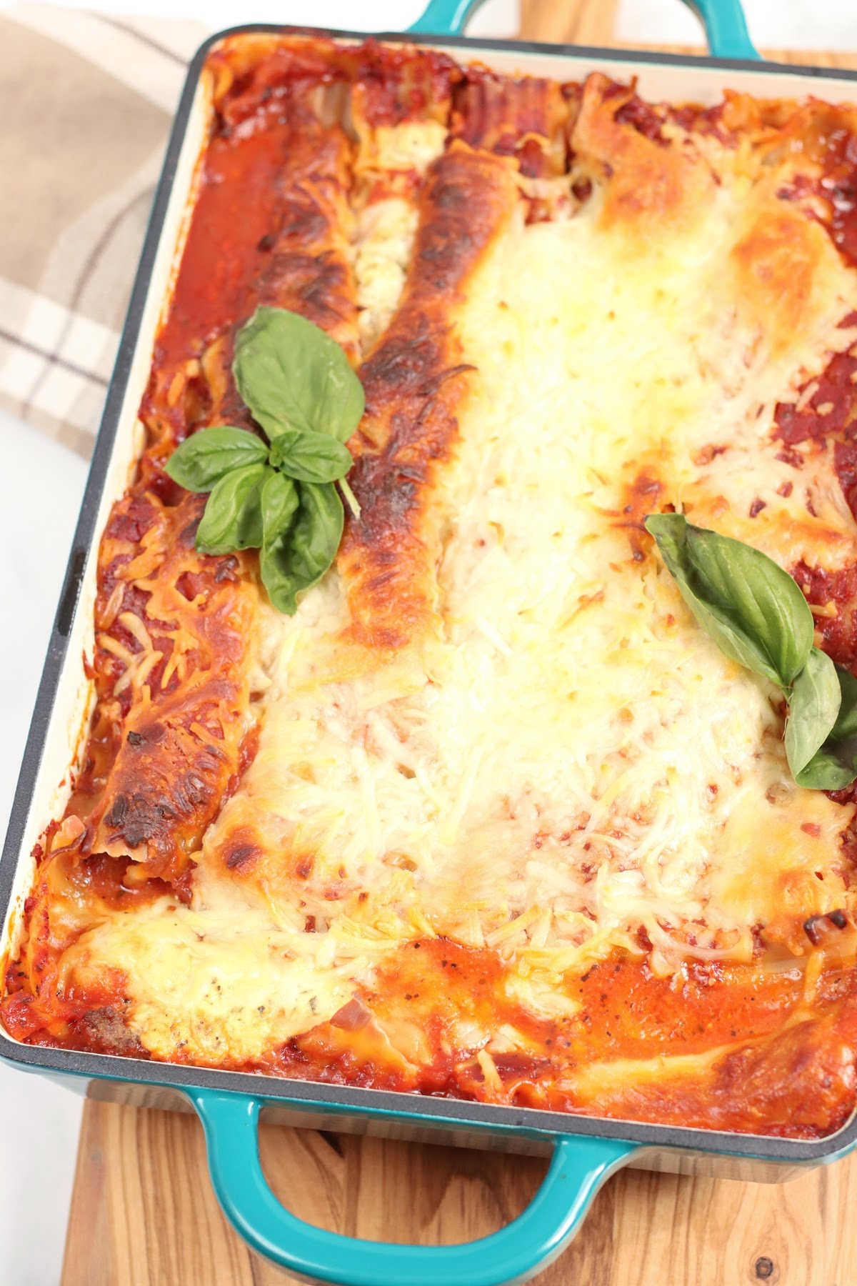Lasagna in teal rectangle cast iron baking dish.