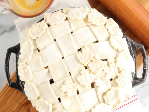 Pie with lattice crust and leaves in dual handle cast iron pie pan.