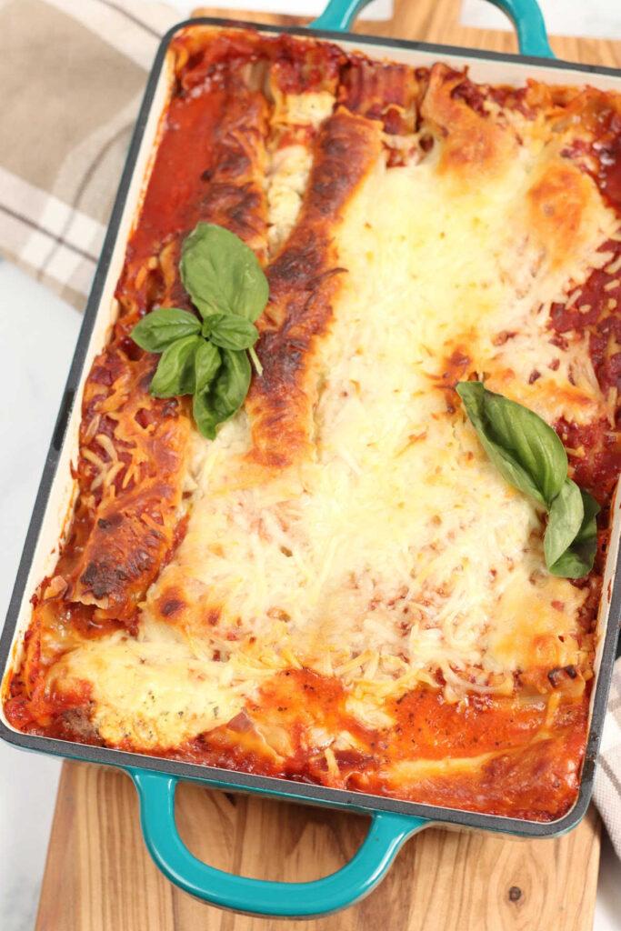 Lasagna in a teal color dual handle rectangle baking dish.