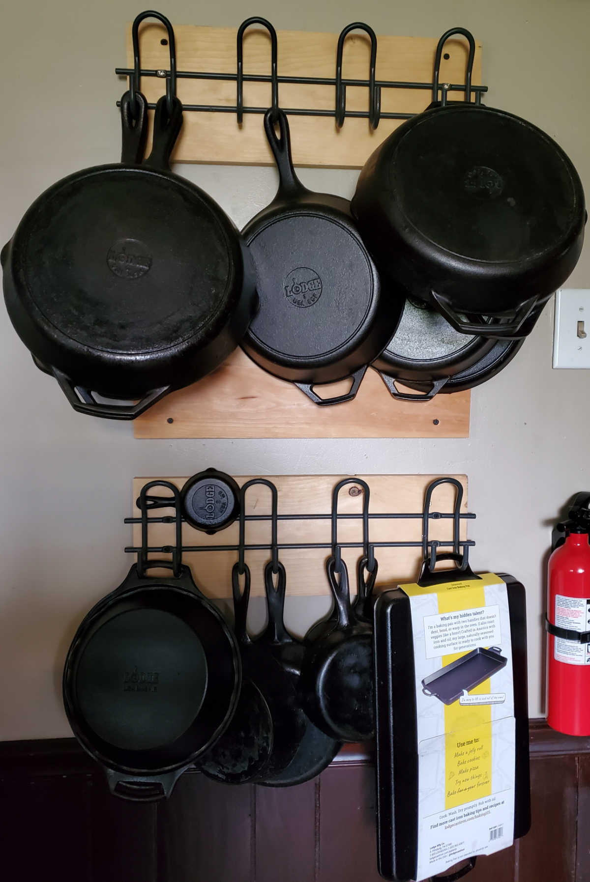 Cast iron skillets hung on metal hooks on kitchen wall.