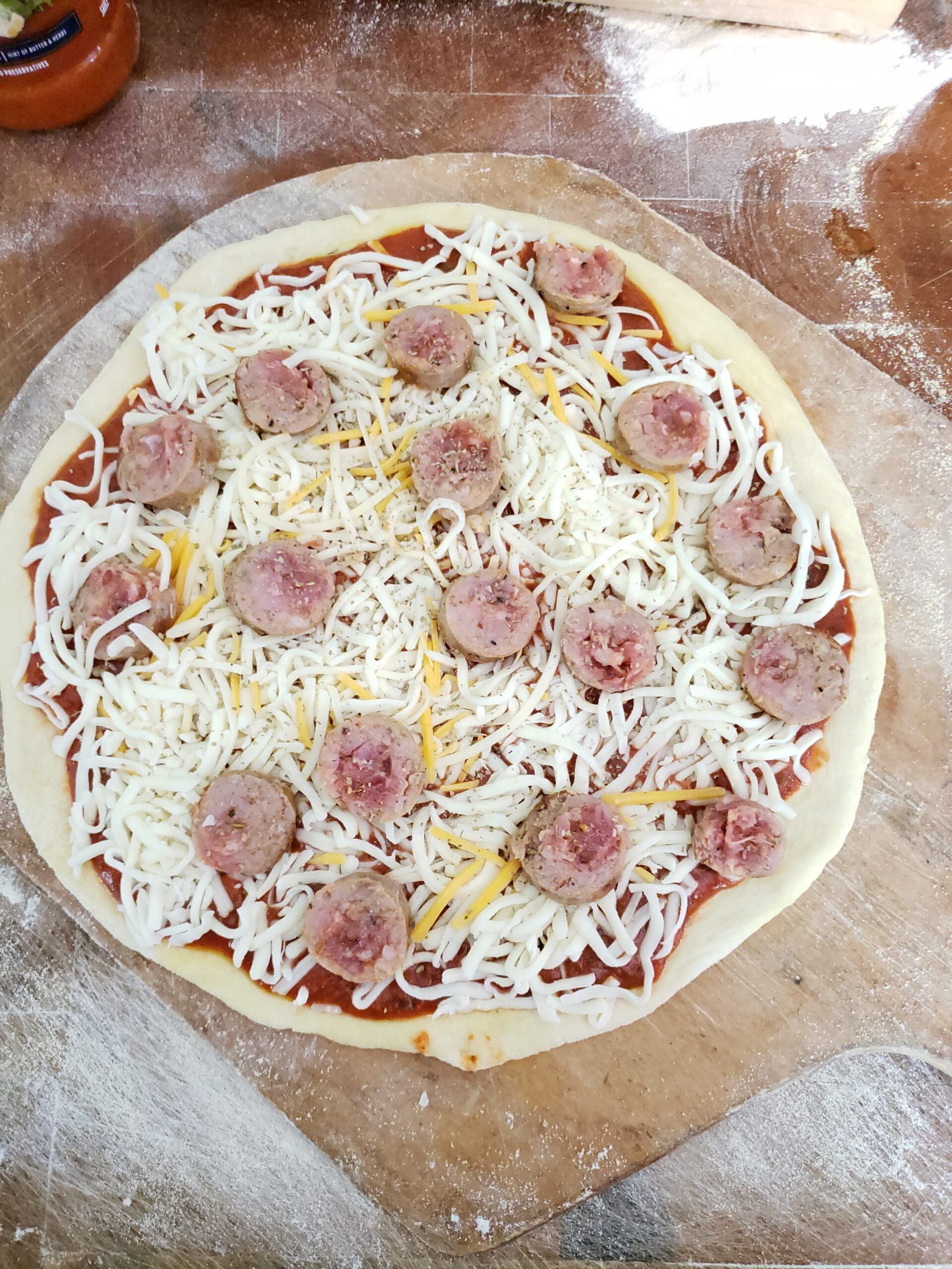 Making a pizza on wooden pizza paddle with cheese and sliced sausage links.
