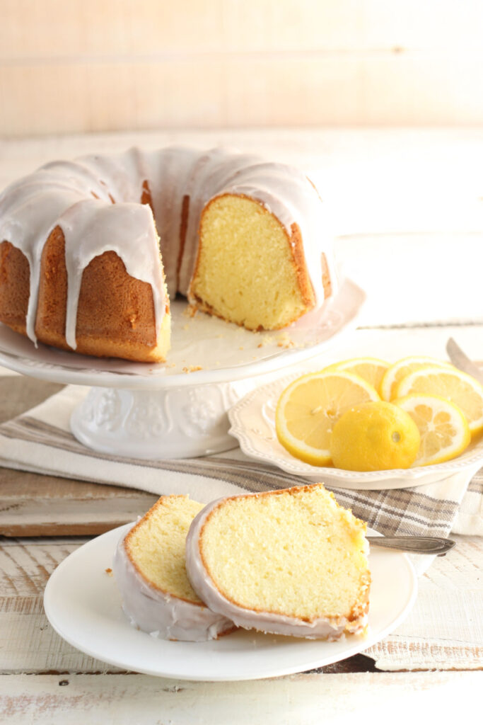 Lemon Bundt cake on white footed cake dish, slices of cake on white plate.