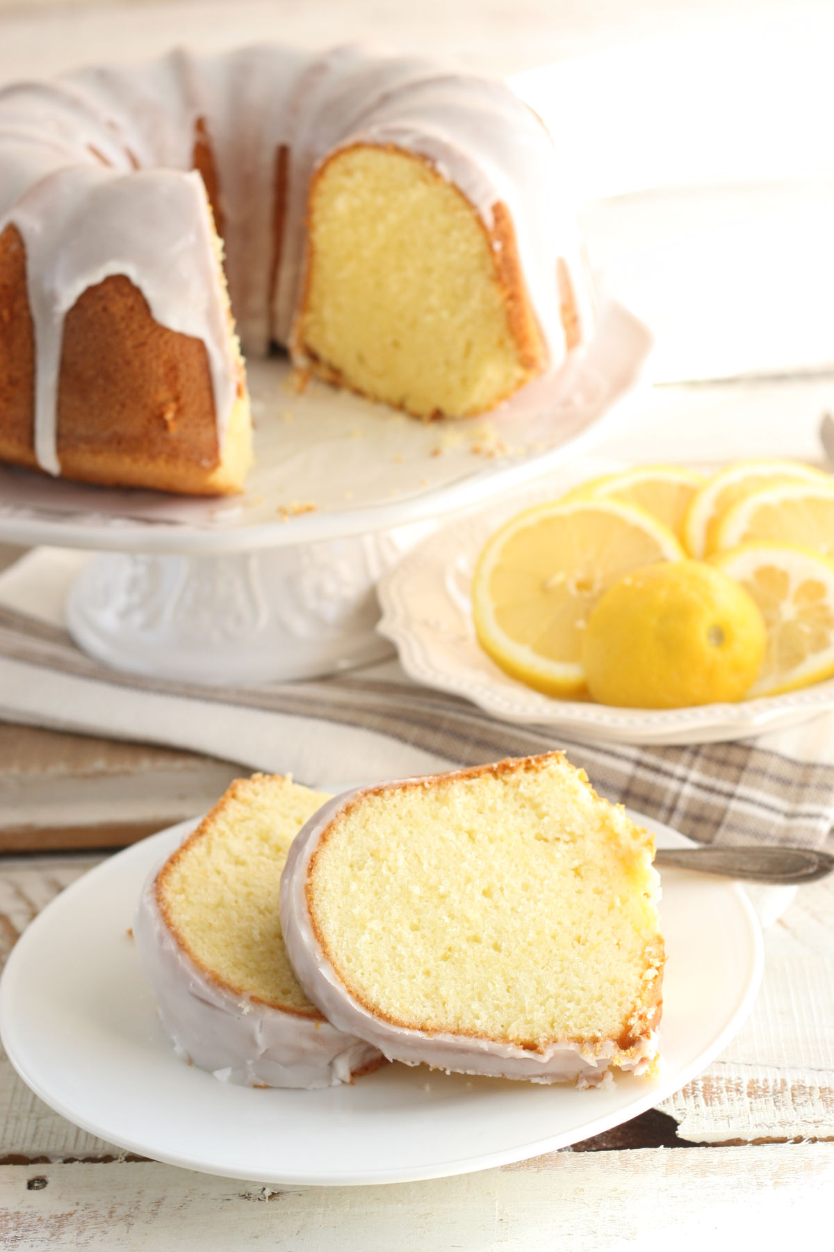 Lemon Bundt cake on white footed cake dish, two slices on small white plate.