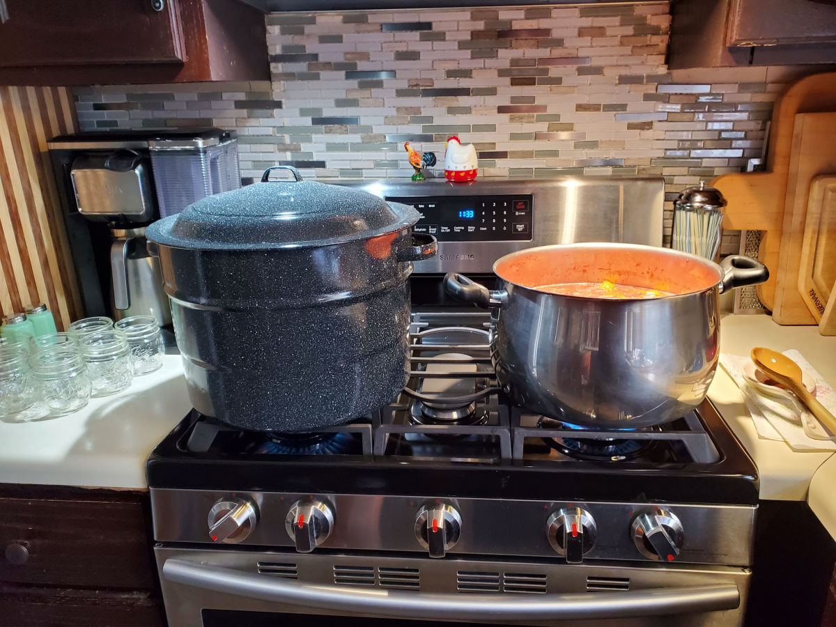 Propane kitchen stove with big pot of jam cooking and enamelware water bath canner.
