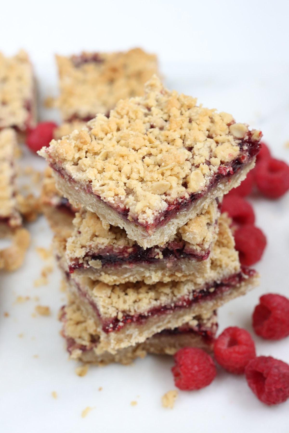 raspberry bars stacked on each other, fresh raspberries around the bottom.