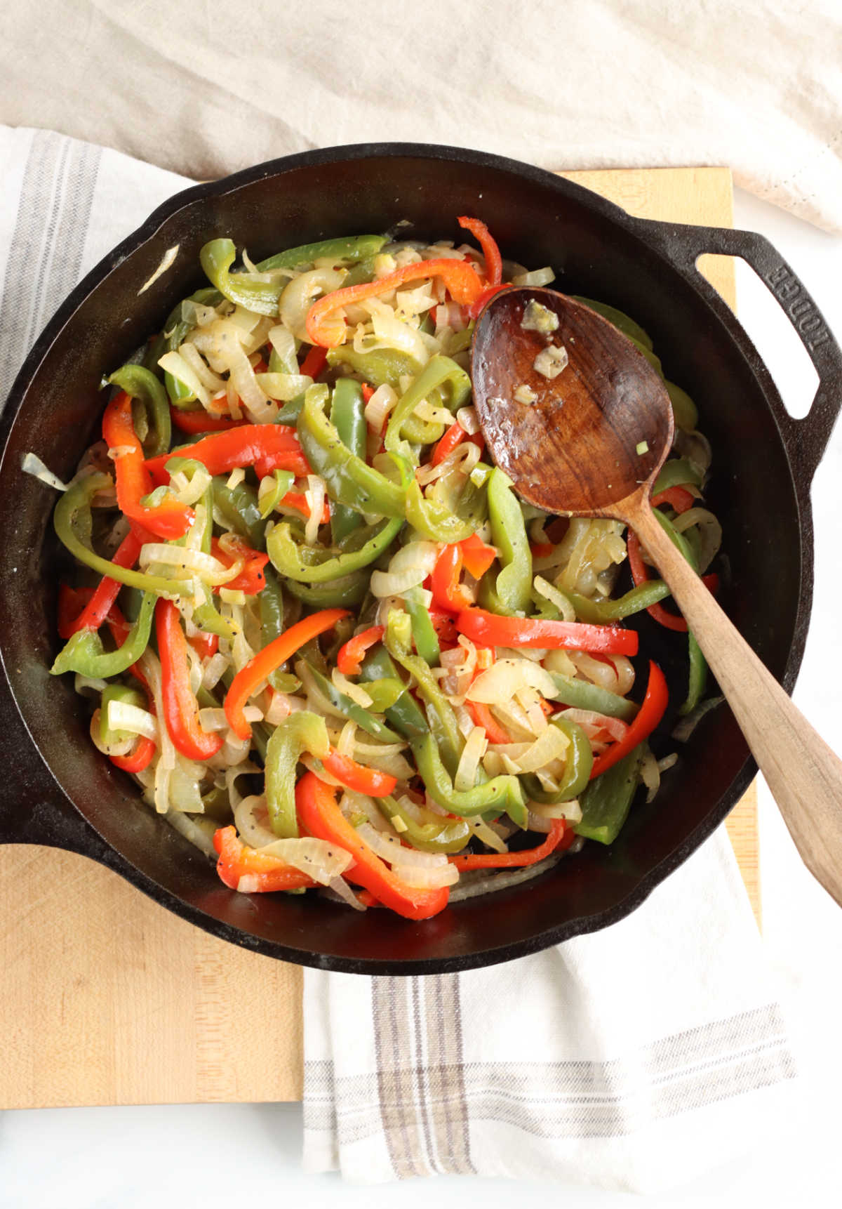 Red and green Bell peppers, onions in large cast iron skillet, wooden spoon in right of pan.