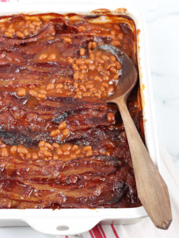 Baked beans in white rectangle baking dish, wooden spoon in dish.