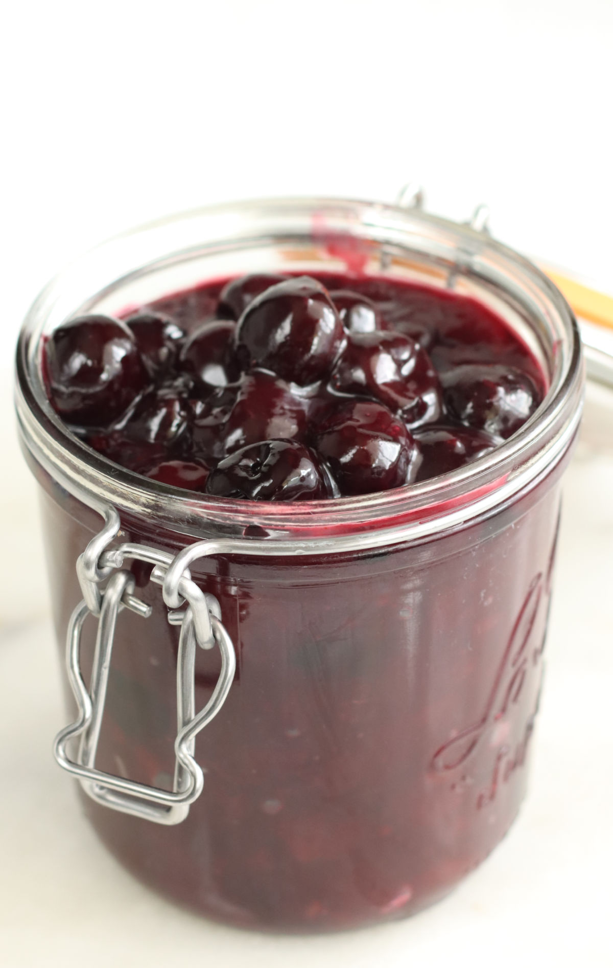 Glass jar of cherry pie filling on white marble.