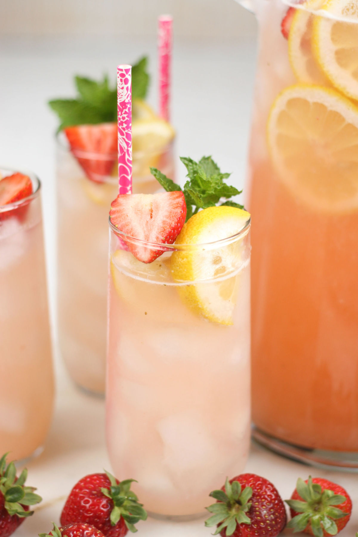 Clear cylinder glass of strawberry lemonade, fresh strawberry slices, ice cubes, lemon slices, fresh mint in glass.