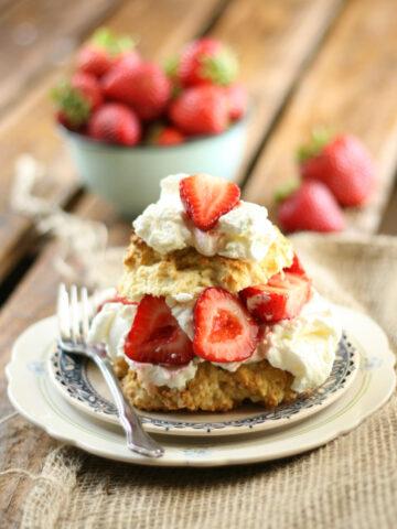 Strawberry shortcake, fresh strawberries, whipped cream on small white plate.