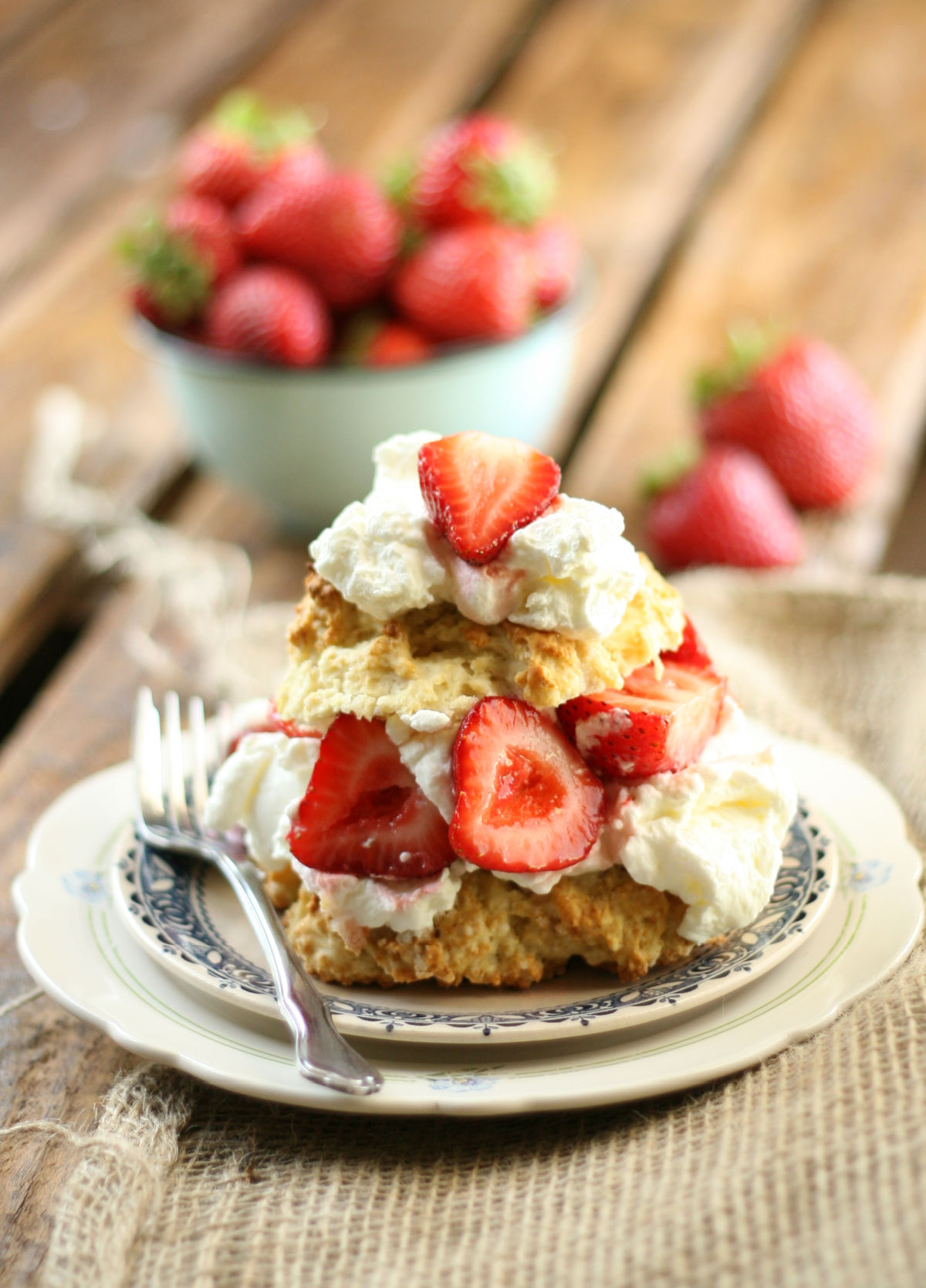 Strawberry shortcake biscuit cut in half with slices of strawberries and whipped cream on small white plate.