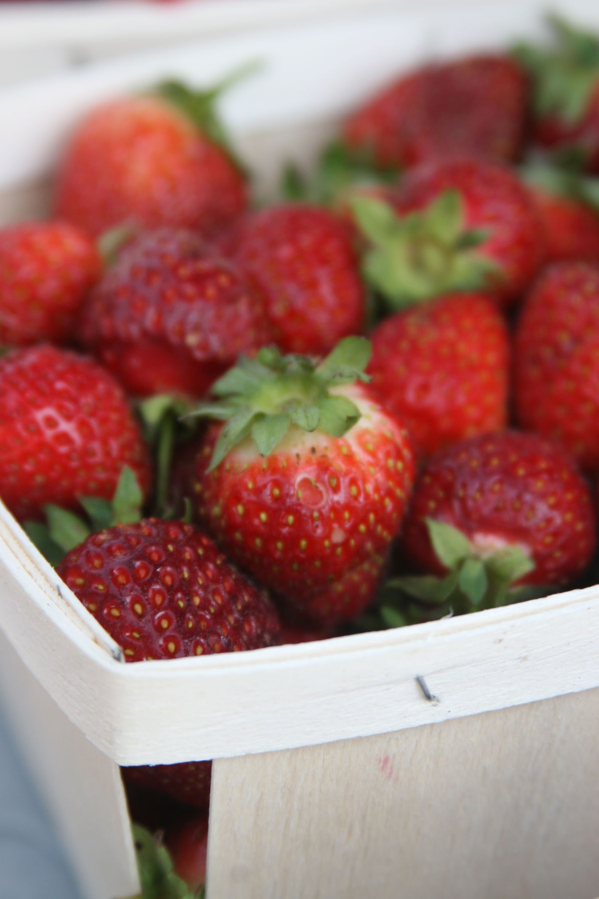 Close up of strawberries in wooden farmers market basket.