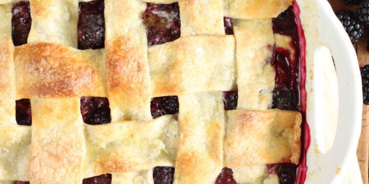 Cobbler with blackberries and lattice pie crust in white baking dish.