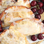 Cherry hand pies with glaze lined up on each other on wooden cutting board.
