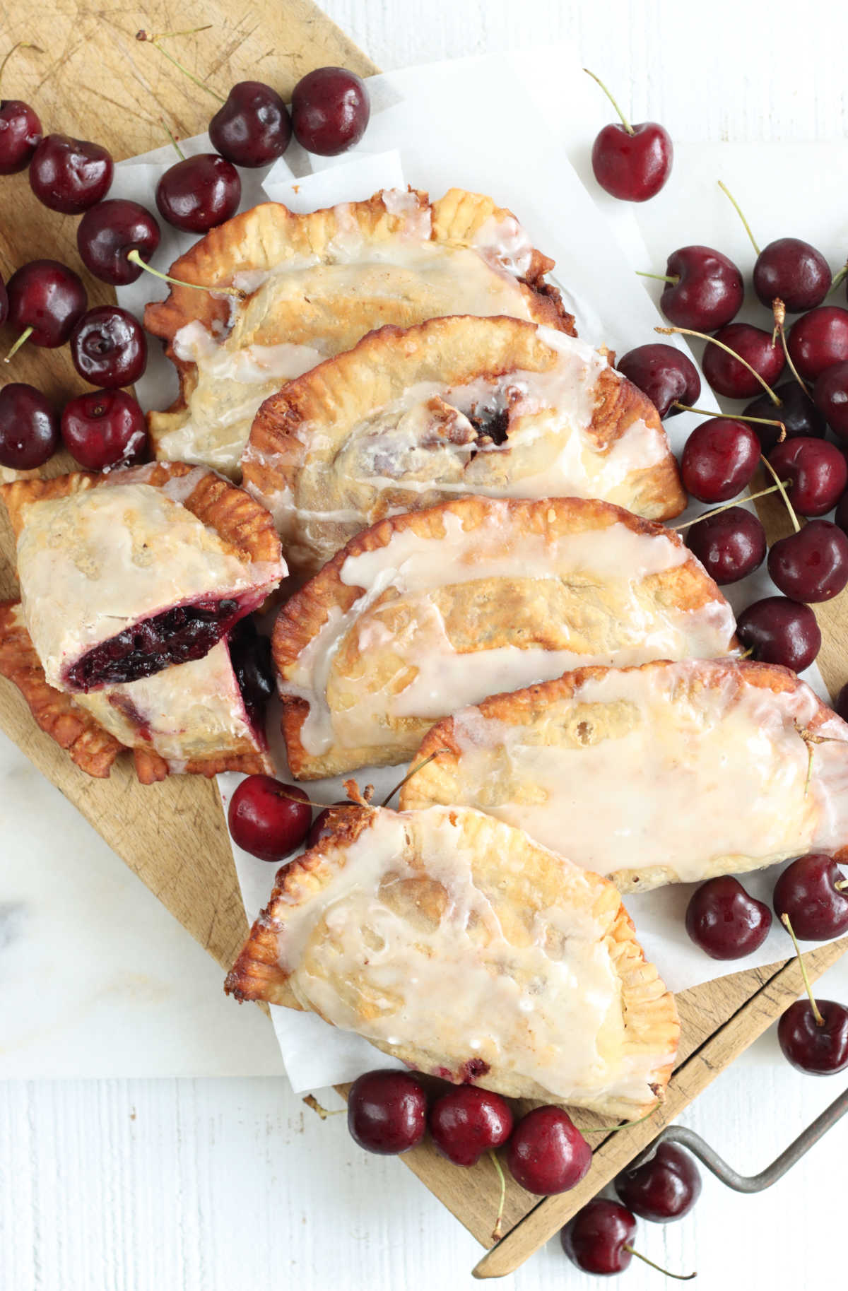 Cherry hand pies leaning against each other on wooden cutting board, fresh cherries around.