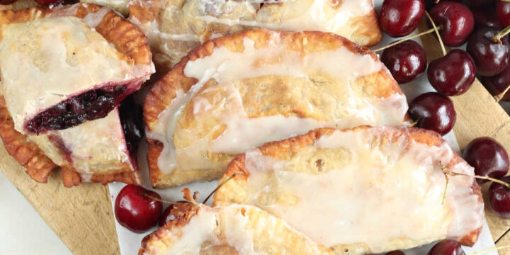 Cherry hand pies on wooden cutting board, fresh cherries around.